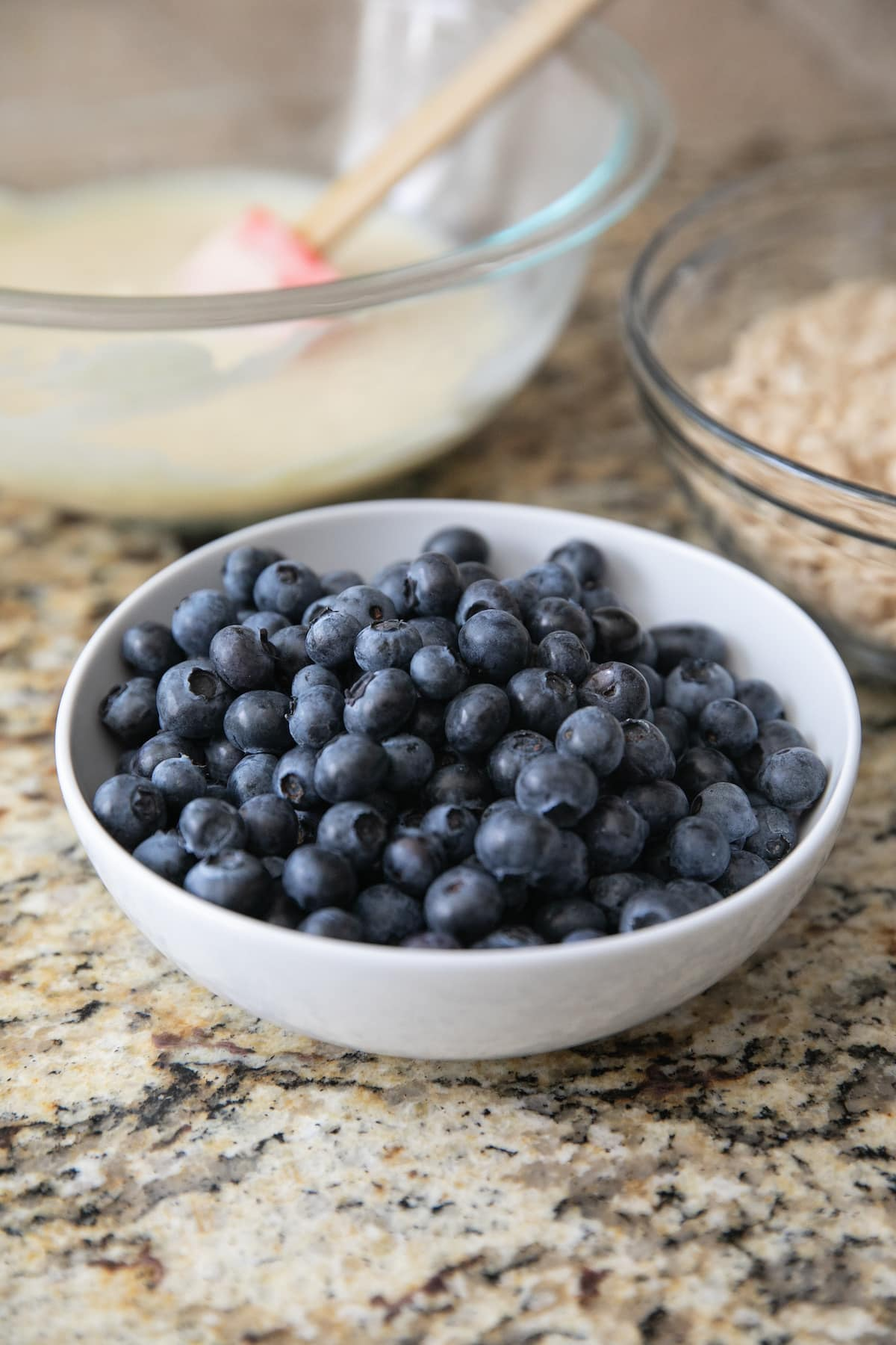 washed room temperature blueberries in a white bowl with two other bowls behind it