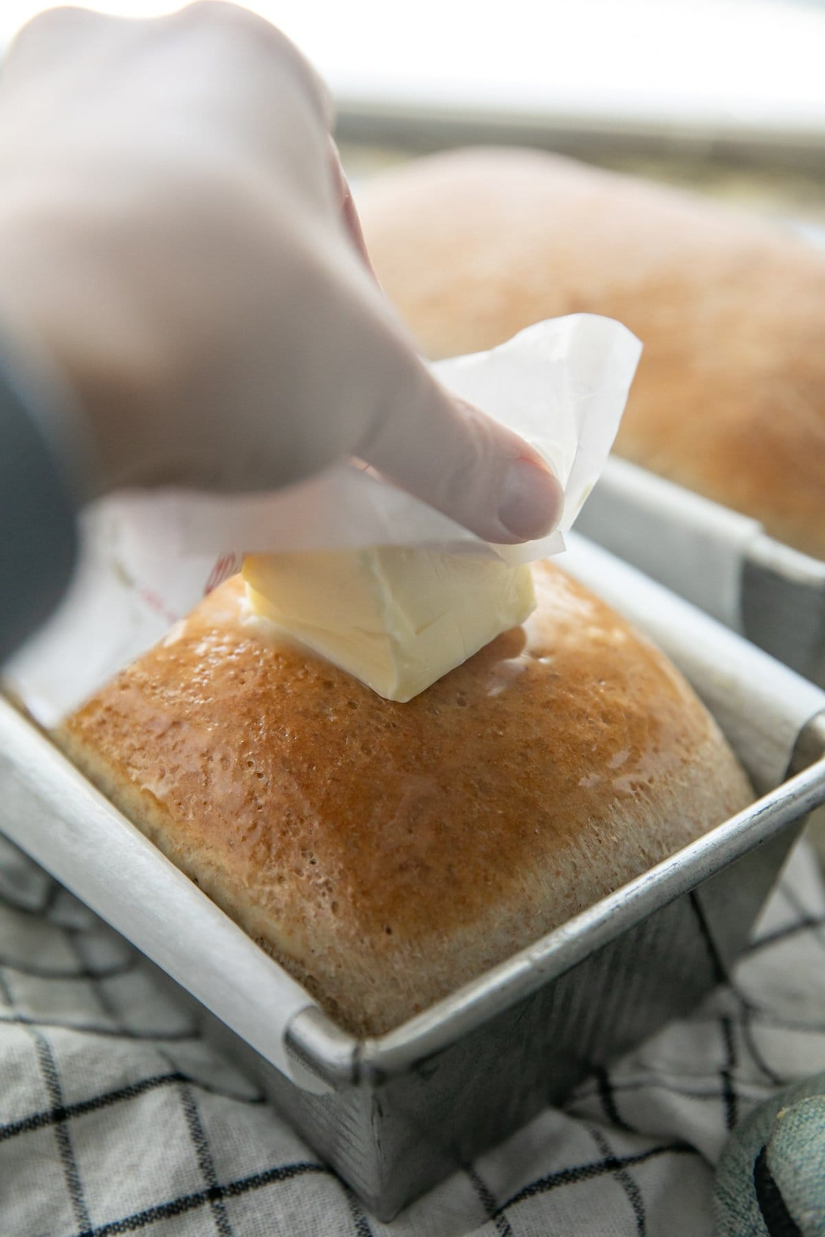 a hand rubbing a stick of butter on a freshly baked loaf of bread still in the pan
