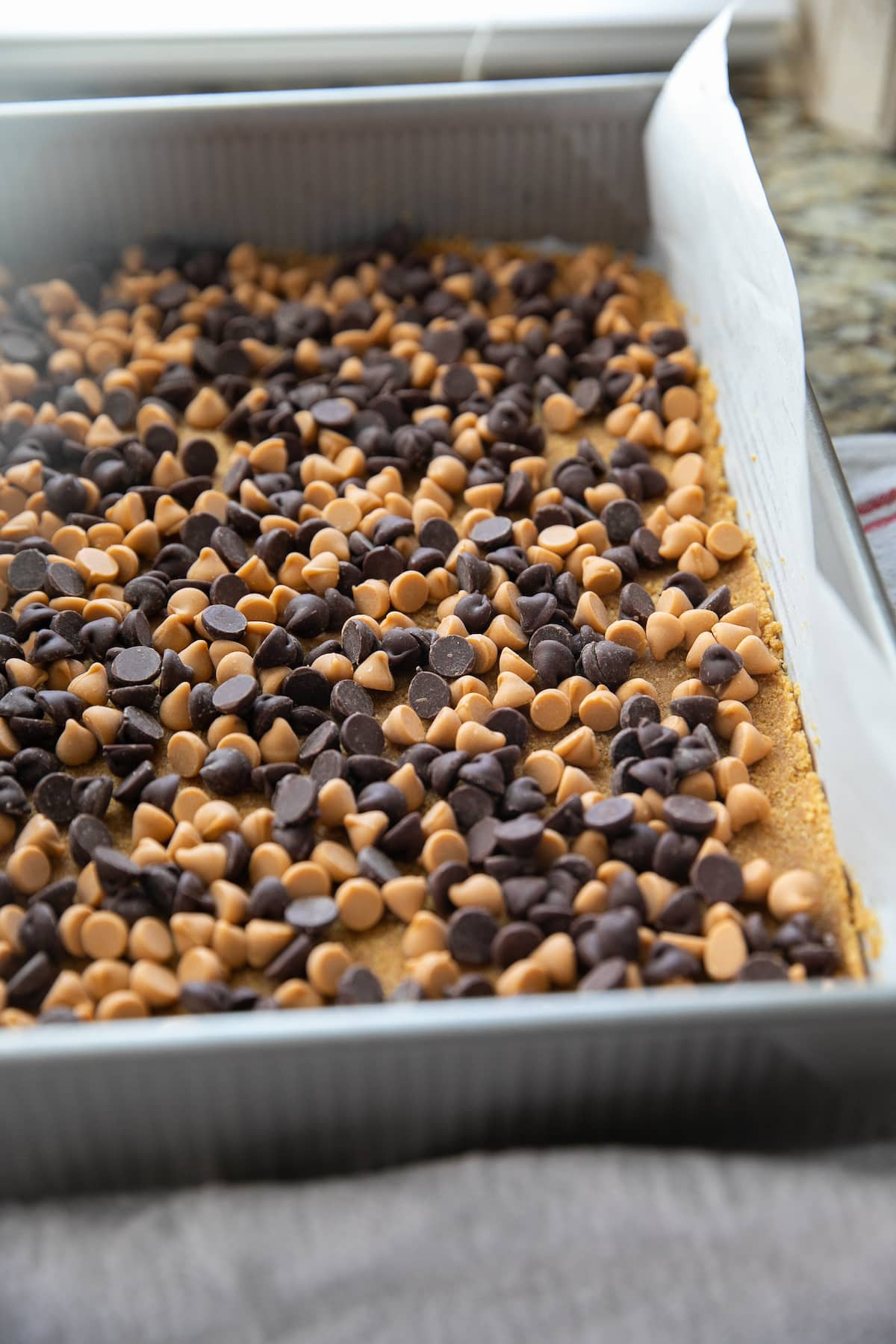 chocolate and butterscotch chips on top of graham cracker crust all in a baking dish