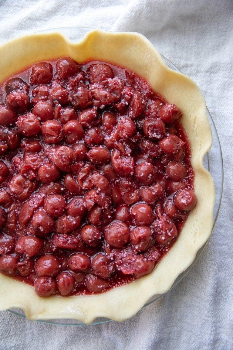 cherry pie filling in pie dough all in a pie baking pan