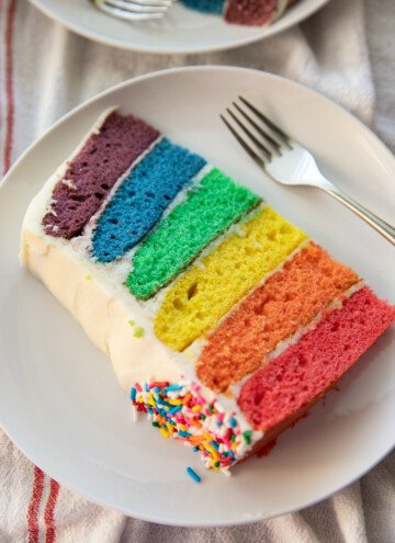 slice of rainbow cake on white plate with fork