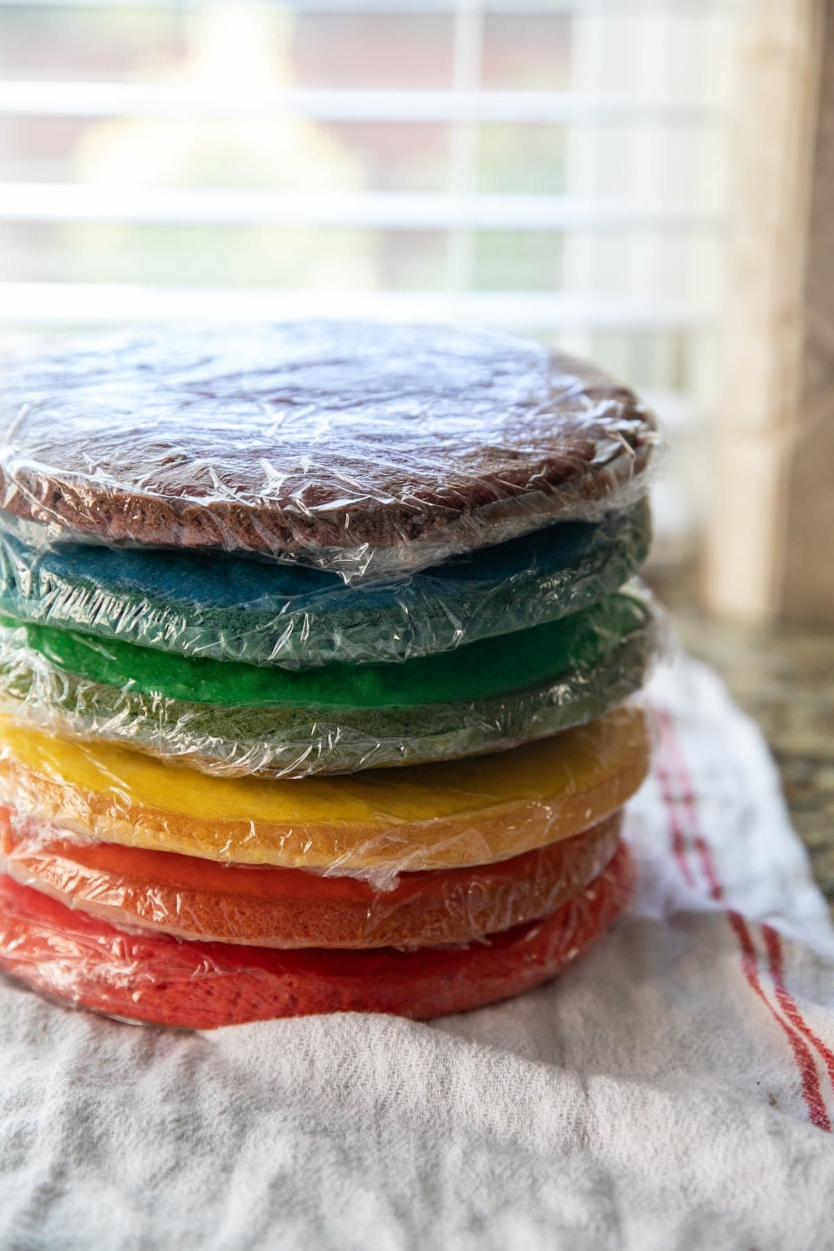 a stack of wrapped cake layers in six different colors
