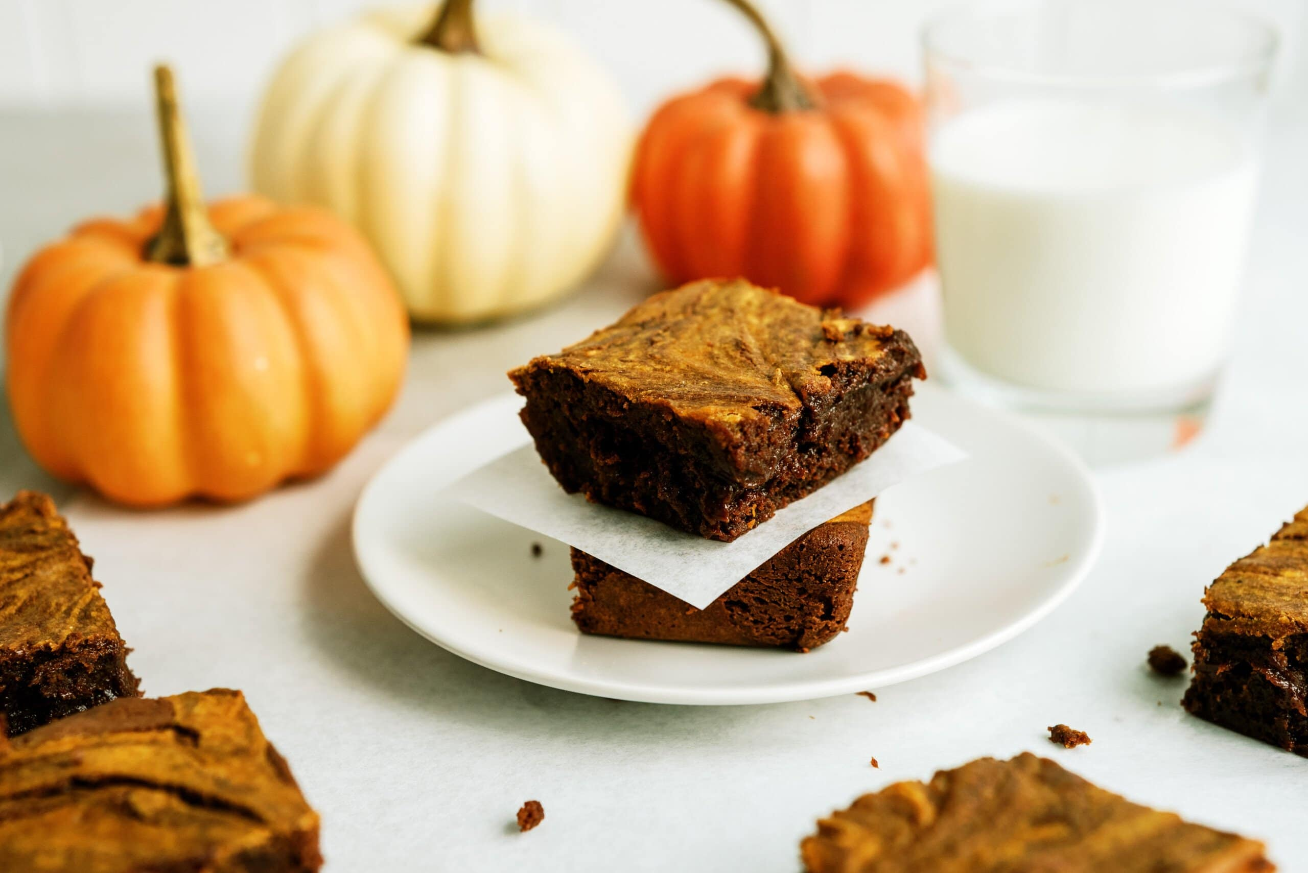 two pumpkin brownies stacked on top of each other separated by parchment paper all on a white plate