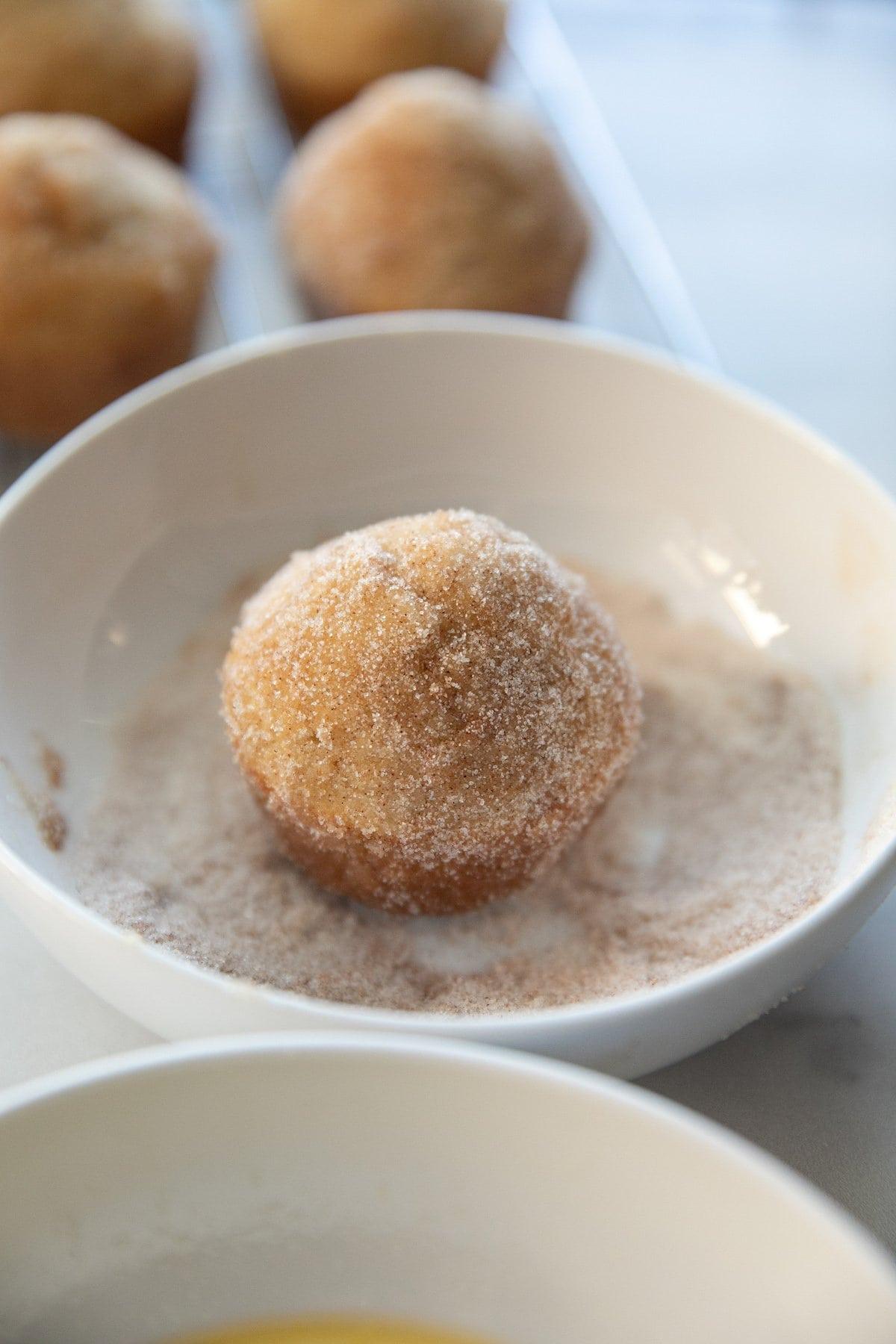 rolling muffin in cinnamon sugar