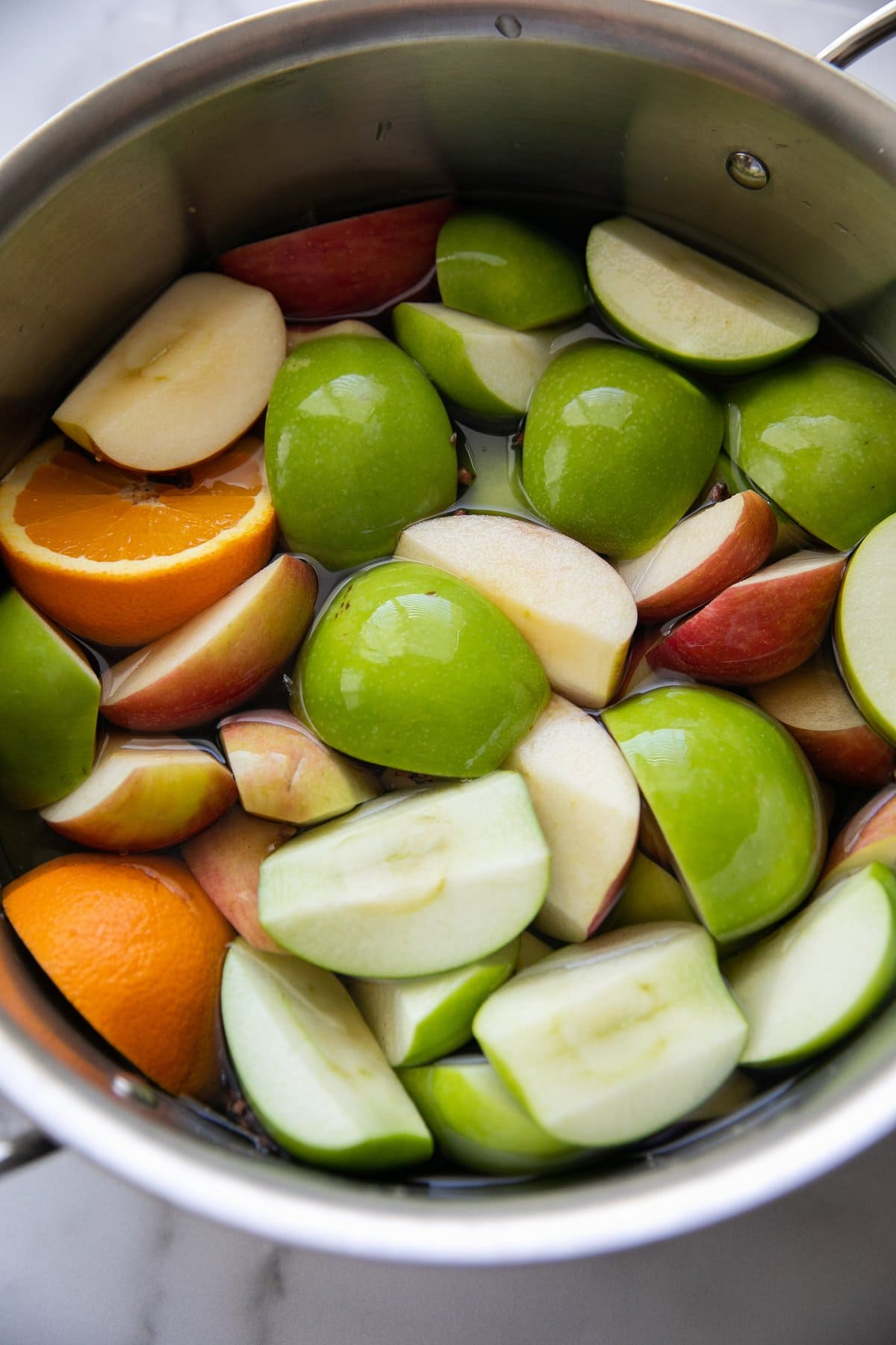 sliced apples and oranges in a pot filled with water