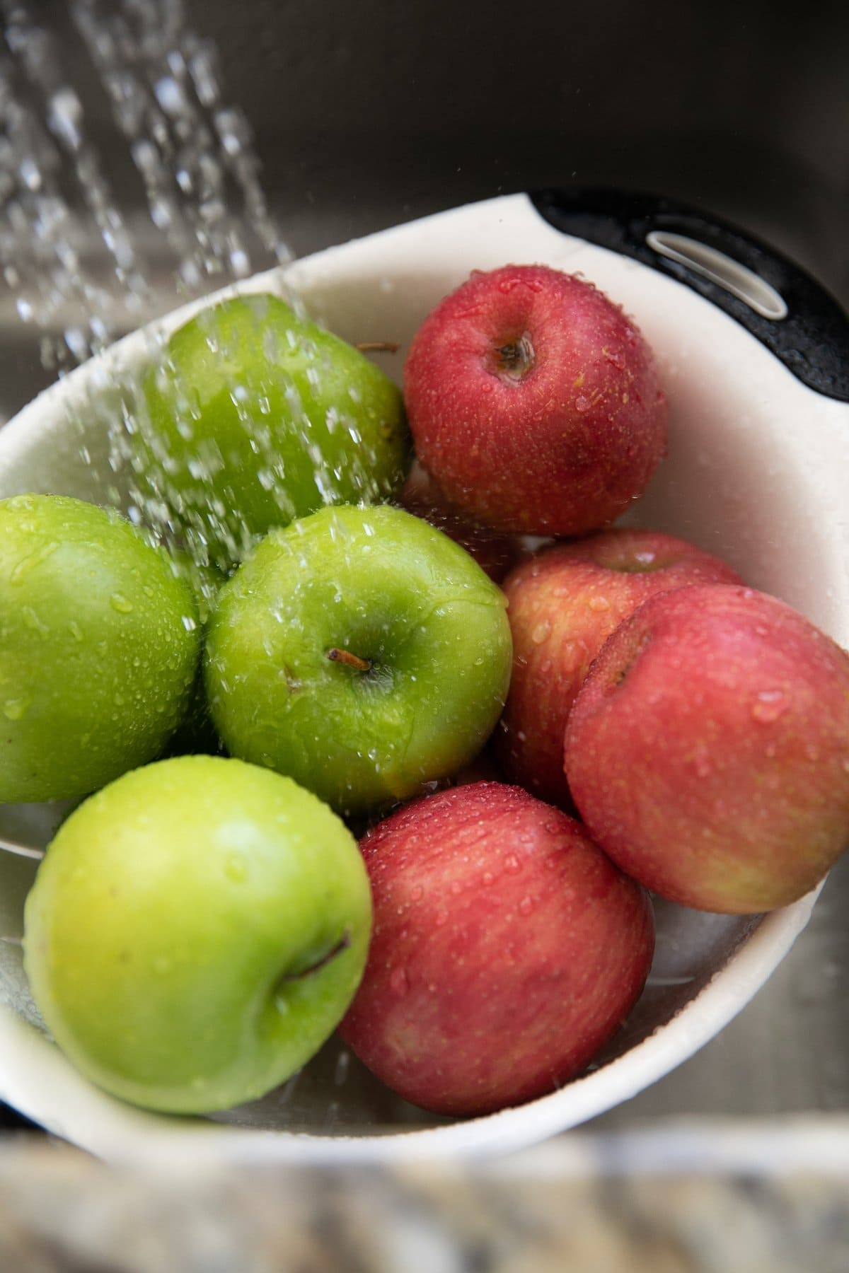 washing apples in a colander