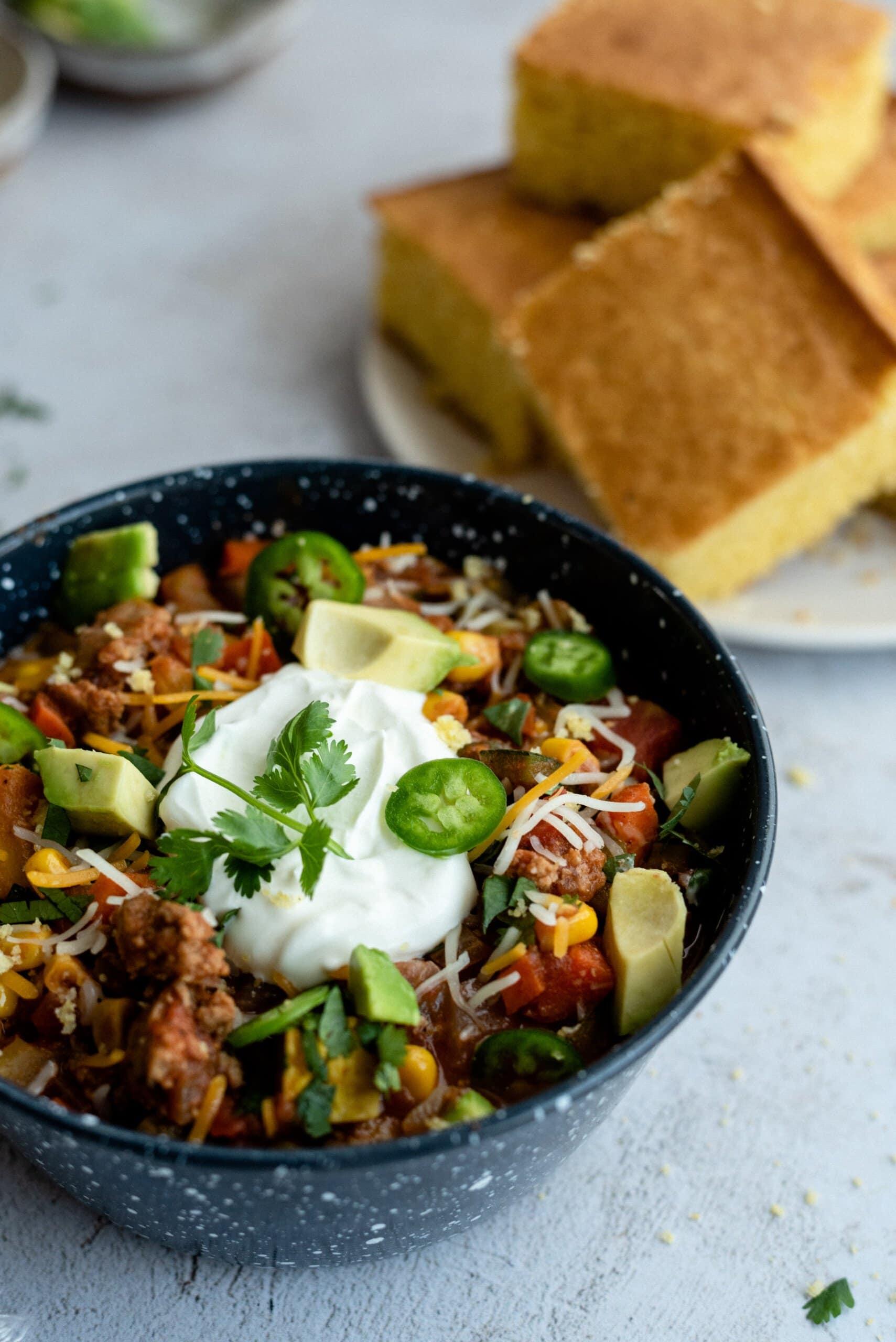 three quarter view of a bowl of chili next to cornbread
