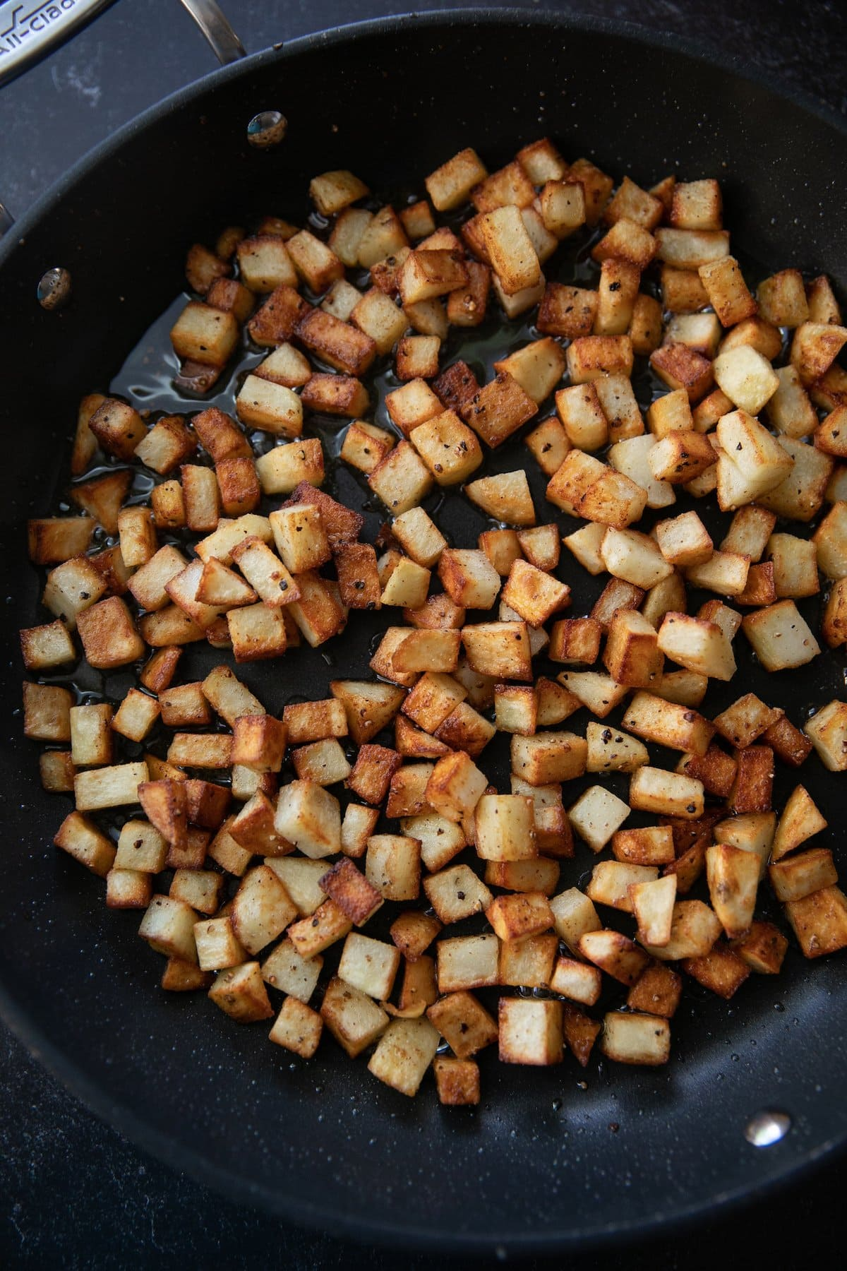 potatoes being fried in a pan