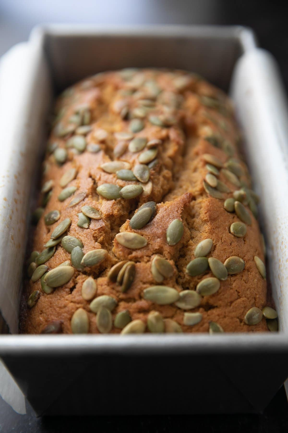 baked pumpkin bread in a parchment paper lined loaf pan topped with pepitas