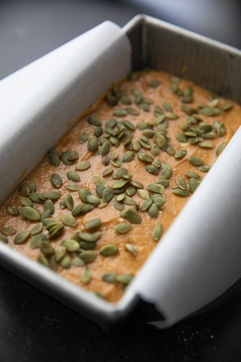 pumpkin. bread batter in a parchment paper lined loaf pan sprinkled with green pepitas