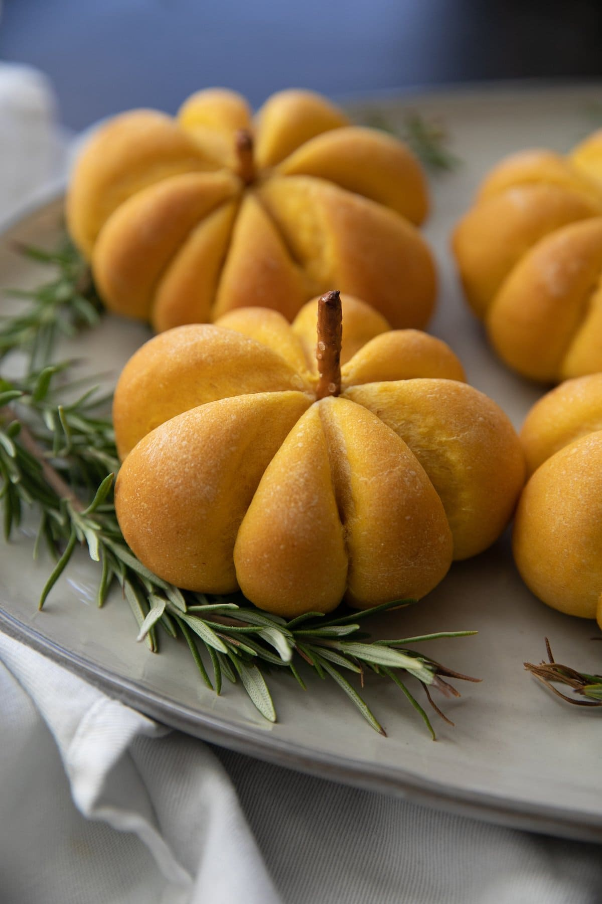 pumpkin bread rolls on a serving plate with greenery