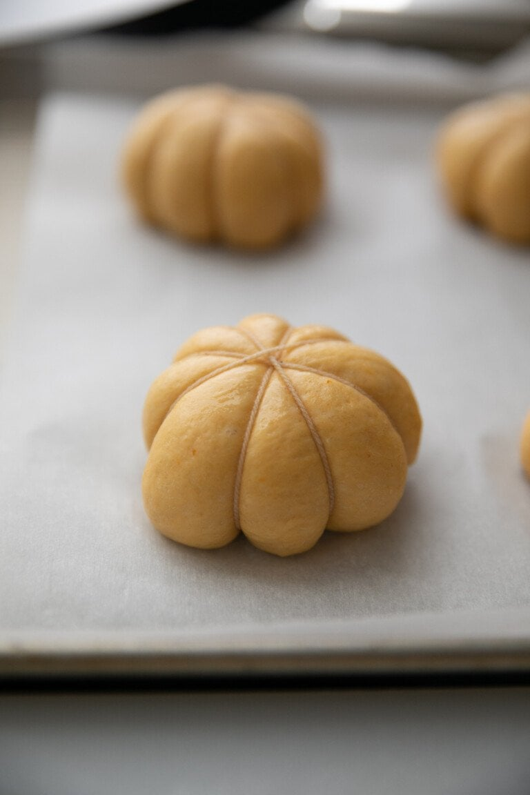 bakers string wrapped around dough ball to make it look like a pumpkin, all on a parchment paper lined baking sheet
