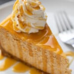 piece of pumpkin cheesecake on a white plate with a caramel drizzle and whipped cream