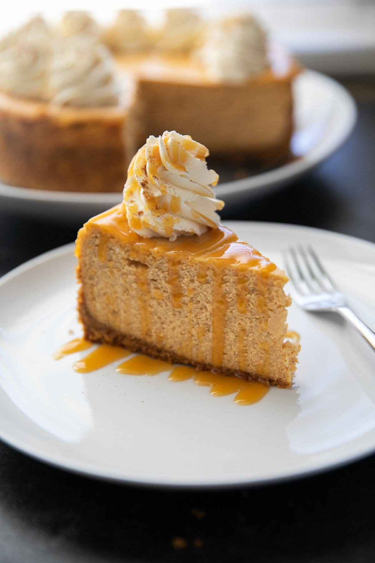 piece of pumpkin cheesecake with a caramel drizzle and whipped cream all on a white plate