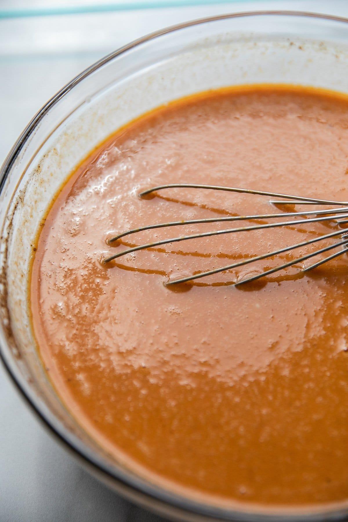 whisking pumpkin cake ingredients in bowl