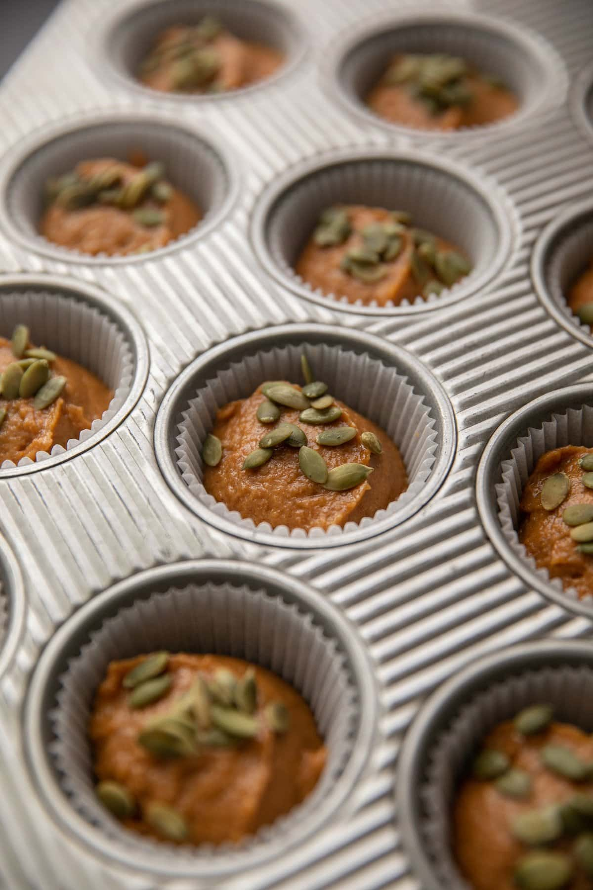 pumpkin muffin batter in muffin tins topped with green pepita seeds
