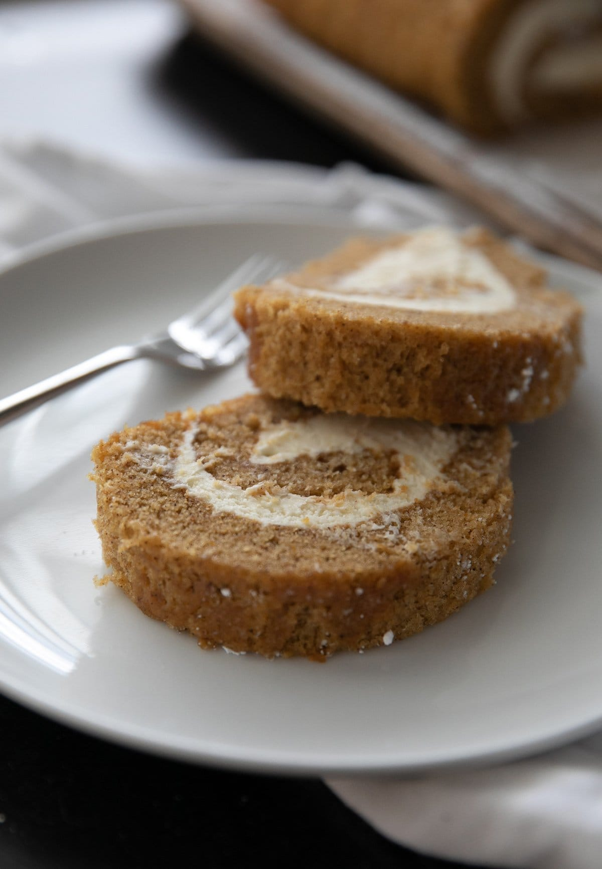 two slices of pumpkin roll cake on a white plate