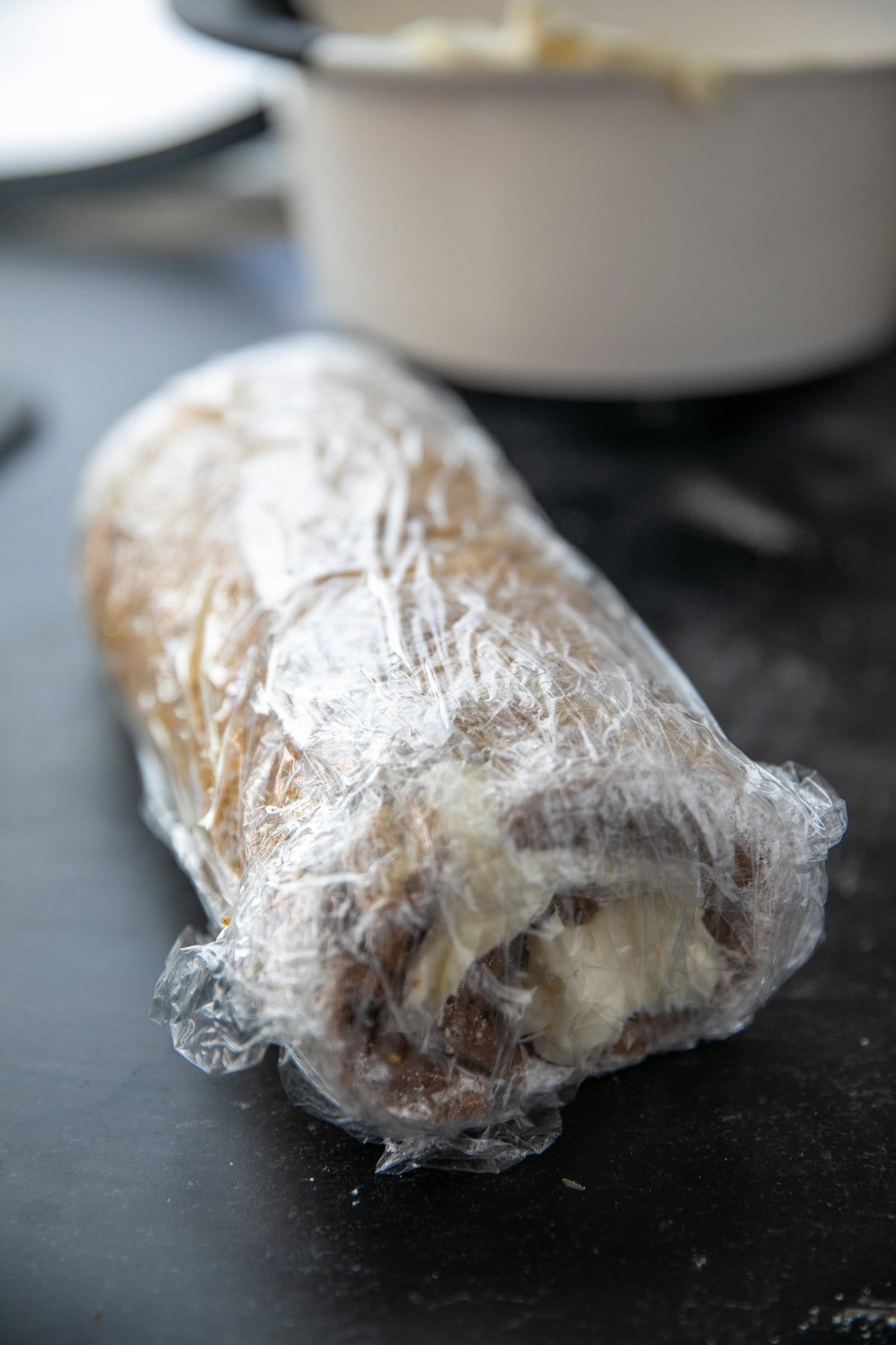 pumpkin roll cake rolled up and wrapped in plastic wrap