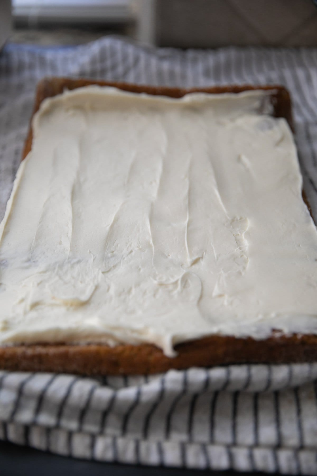 pumpkin roll cake with cream cheese filling spread over it unrolled
