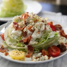 wedge salad with toppings and dressing on a white plate