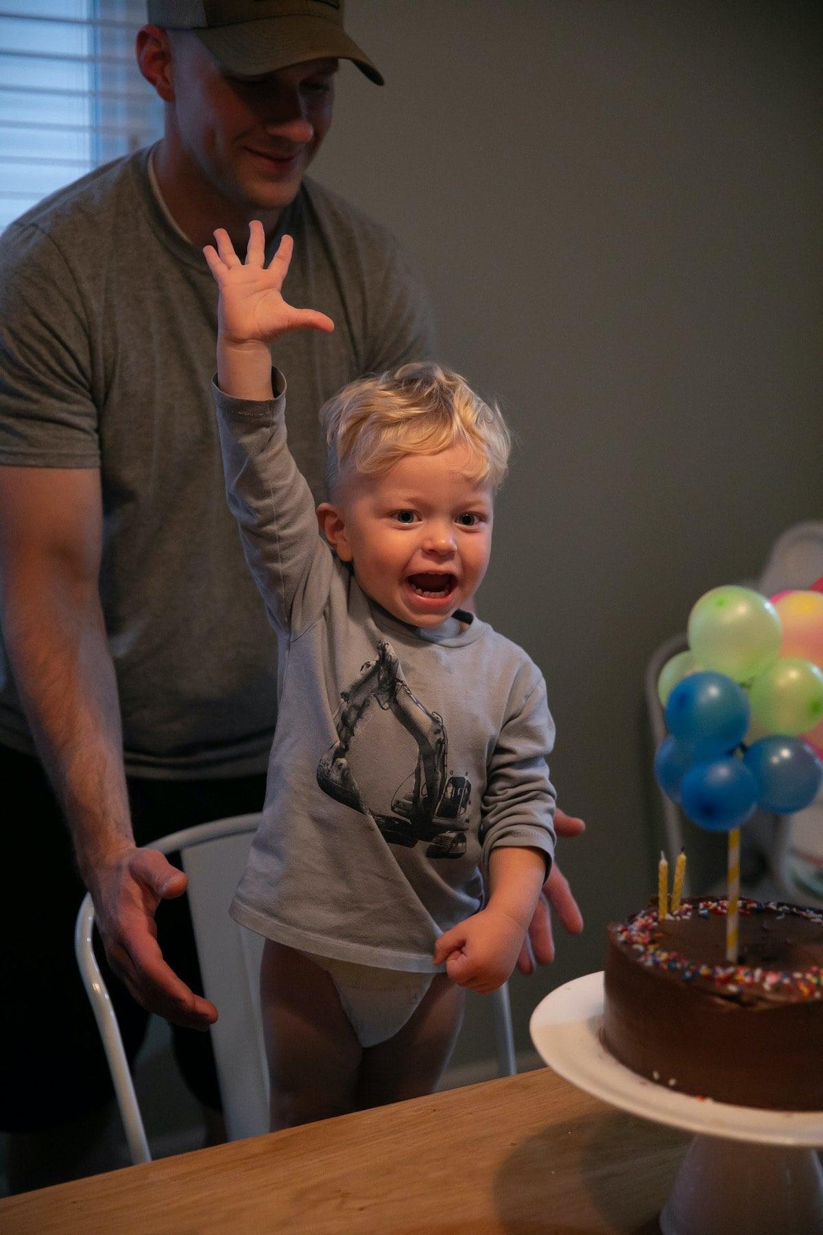 baby raising his hand in front of birthday cake
